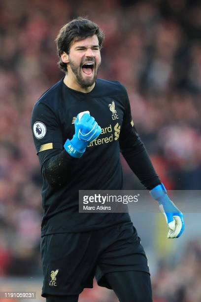 Alisson Becker of Liverpool celebrates team mate Virgil van Dijk's goal during the Premier League match between Liverpool FC and Brighton Hove Albion...