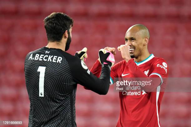 Alisson Becker of Liverpool celebrates with Fabinho after the Premier League match between Liverpool and Tottenham Hotspur at Anfield on December 16,...