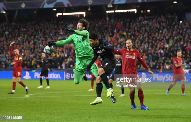 Alisson Becker of Liverpool claims the ball under pressure from Hwang Heechan of Red Bull Salzburg during the UEFA Champions League group E match...