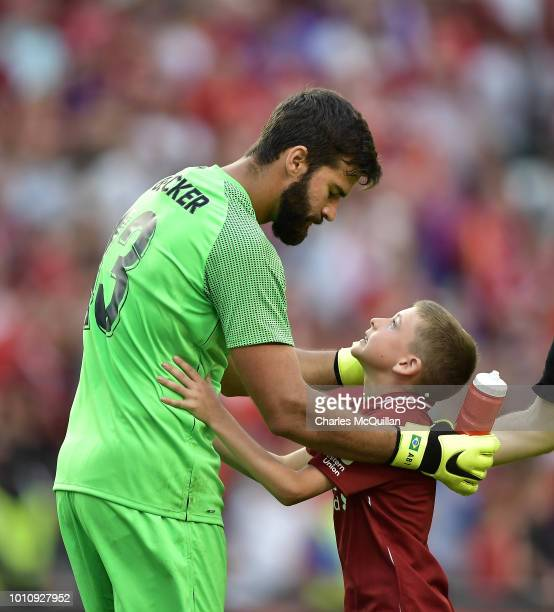 Alisson Becker of Liverpool embraces a young supporter who had run on to the pitch during the international friendly game between Liverpool and...