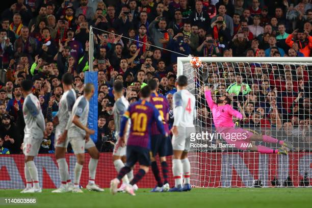 Alisson Becker of Liverpool fails to stop Lionel Messi of FC Barcelona from scoring a goal to make it 30 and his 600th goal for Barcelona during the...
