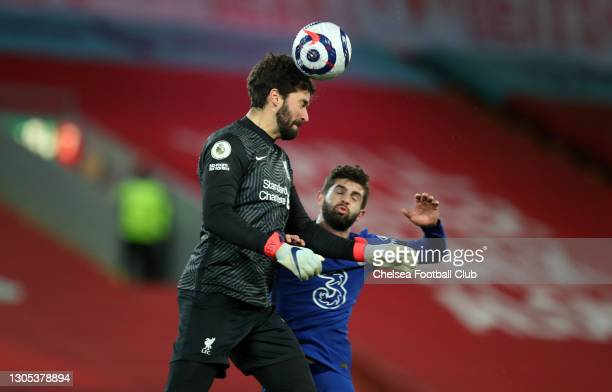 Alisson Becker of Liverpool heads the ball under pressure from Christian Pulisic of Chelsea during the Premier League match between Liverpool and...