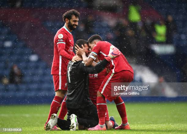 Alisson Becker of Liverpool is congratulated on scoring the winning goal by Mohamed Salah, Thiago Alcantara and Roberto Firmino during the Premier...