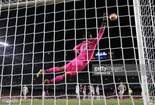 Alisson Becker of Liverpool is unable to save the free kick from Lionel Messi of Barcelona who scores his sides third goal during the UEFA Champions...