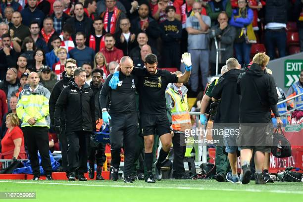 Alisson Becker of Liverpool leaves the pitch following an injury during the Premier League match between Liverpool FC and Norwich City at Anfield on...