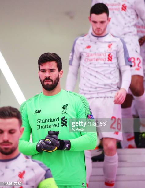 Alisson Becker of Liverpool lines up with his team mates before the UEFA Champions League Round of 16 Second Leg match between FC Bayern Muenchen and...