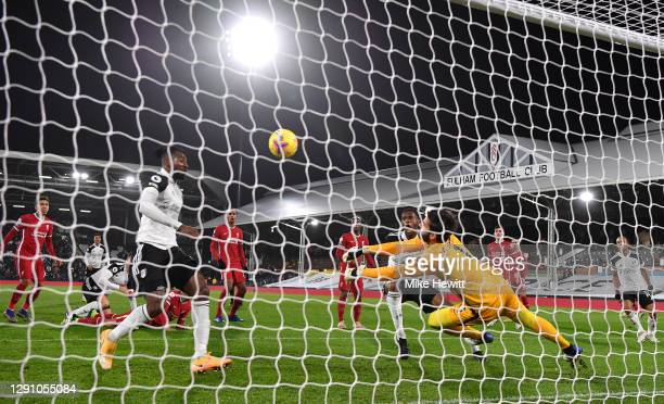Alisson Becker of Liverpool makes a save from Tosin Adarabioyo of Fulham during the Premier League match between Fulham and Liverpool at Craven...
