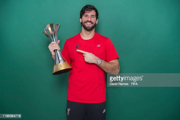 Alisson Becker of Liverpool poses with the Club World Cup trophy after the FIFA Club World Cup Qatar 2019 Final match between Liverpool and CR...
