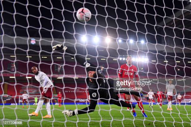 Alisson Becker of Liverpool reaches for the ball as Alexandre Lacazette of Arsenal scores his sides first goal during the Premier League match...