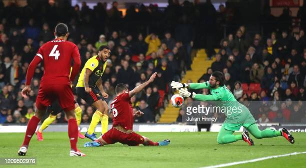 Alisson Becker of Liverpool saves a shot from Troy Deeney of Watford during the Premier League match between Watford FC and Liverpool FC at Vicarage...