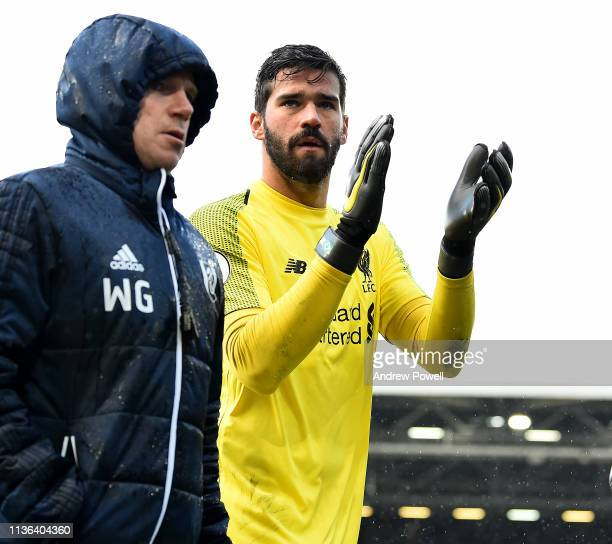 Alisson Becker of Liverpool shows his appreciation to the fans at the end of the Premier League match between Fulham FC and Liverpool FC at Craven...