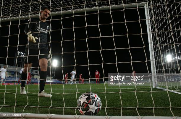 Alisson Becker of Liverpool walks back to collect the ball after conceding their third goal which was scored by Vinicius Junior of Real Madrid during...