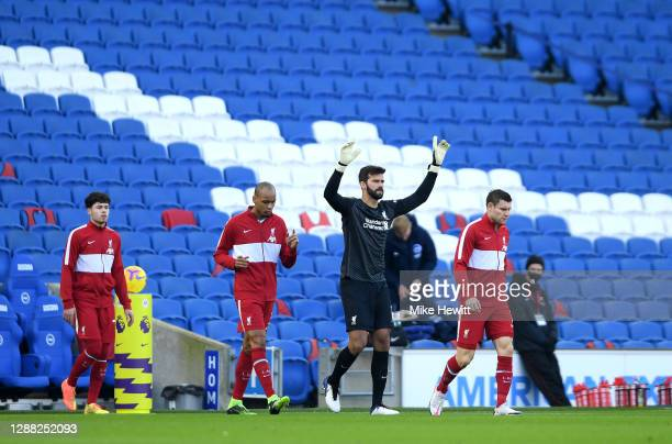 Alisson Becker of Liverpool walks out onto the pitch with teammates James Milner, Neco Williams and Fabinho during the Premier League match between...