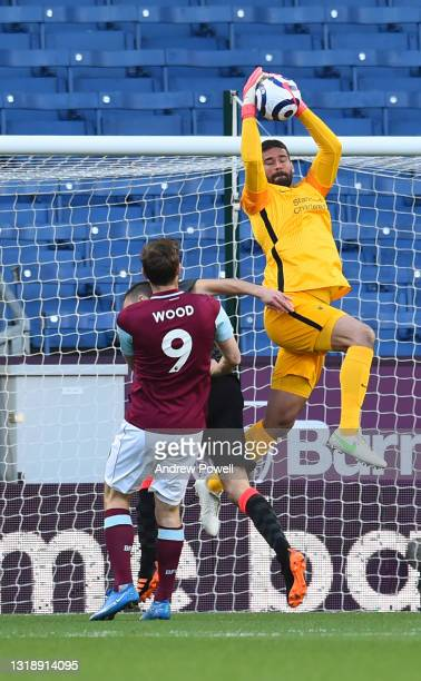 Alisson Becker of Liverpool with Burnley's Chris Wood during the Premier League match between Burnley and Liverpool at Turf Moor on May 19, 2021 in...