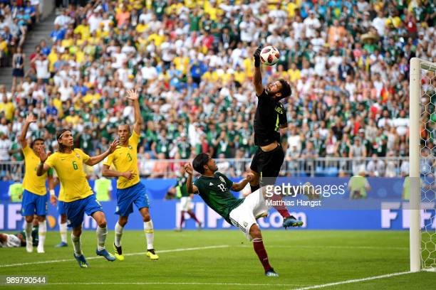 Alisson of Brazil makes a save under pressure from Carlos Vela of Mexico during the 2018 FIFA World Cup Russia Round of 16 match between Brazil and...