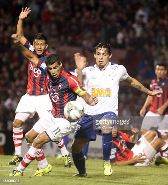 Alisson of Cruzeiro competes for the ball with Carlos Bonet and Luis Cardoso of Cerro Porteño during a match between Cerro Porteno and Cruzeiro as...