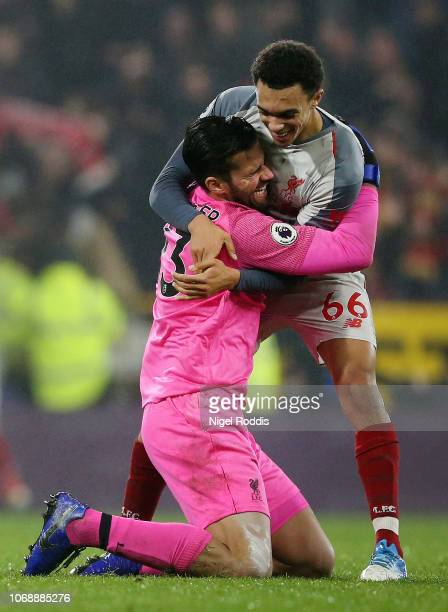 Alisson of Liverpool and Trent AlexanderArnold of Liverpool celebrate following their sides victory in the Premier League match between Burnley FC...