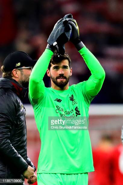 Alisson of Liverpool applauds the crowd after the UEFA Champions League Round of 16 Second Leg match between FC Bayern Muenchen and Liverpool at...