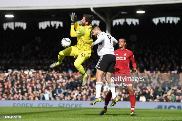 Alisson of Liverpool battles for possession with Aleksandar Mitrovic of Fulham during the Premier League match between Fulham FC and Liverpool FC at...