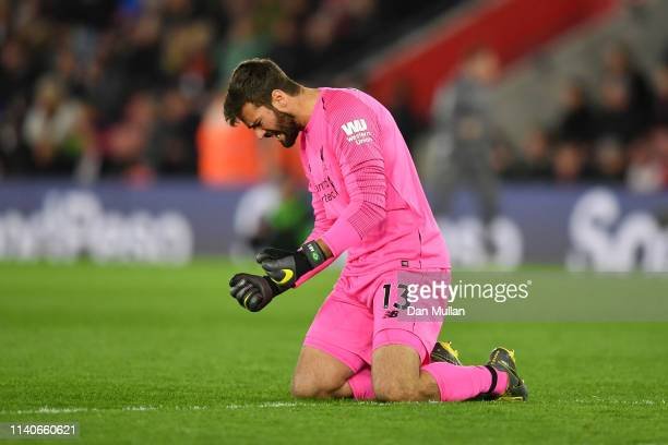 Alisson of Liverpool celebrates after Jordan Henderson of Liverpool scored their team's third goal during the Premier League match between...