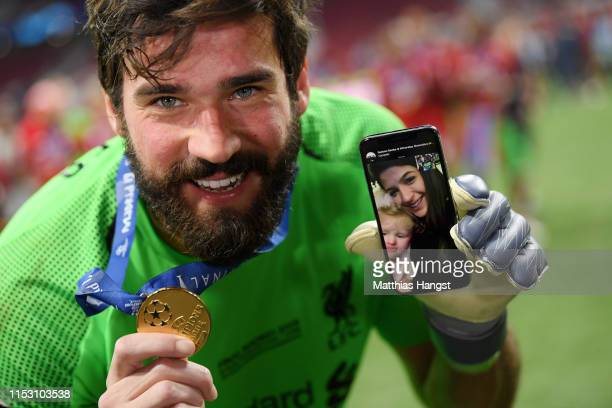 Alisson of Liverpool celebrates with his phone on the pitch after the UEFA Champions League Final between Tottenham Hotspur and Liverpool at Estadio...