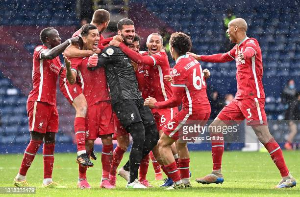 Alisson of Liverpool celebrates with Roberto Firmino, Thiago and team mates after scoring their side's second goal during the Premier League match...