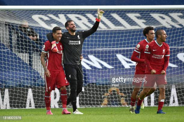 Alisson of Liverpool celebrates with team mate Roberto Firmino after scoring their side's second goal during the Premier League match between West...