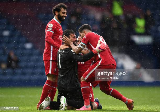 Alisson of Liverpool celebrates with team mates Mohamed Salah and Roberto Firmino after scoring their side's second goal during the Premier League...