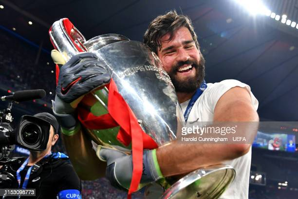 Alisson of Liverpool celebrates with the Champions League Trophy after winning the UEFA Champions League Final between Tottenham Hotspur and...