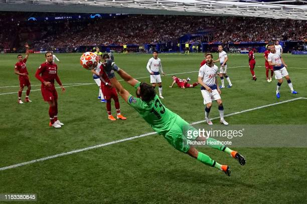 Alisson of Liverpool dives to make a save during the UEFA Champions League Final between Tottenham Hotspur and Liverpool at Estadio Wanda...