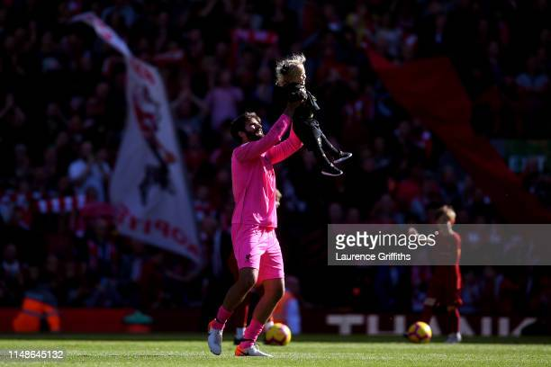 Alisson of Liverpool holds his child up in the air after the Premier League match between Liverpool FC and Wolverhampton Wanderers at Anfield on May...