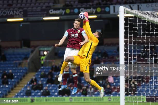 Alisson of Liverpool jumps to catch the ball whilst under pressure from Chris Wood of Burnley during the Premier League match between Burnley and...