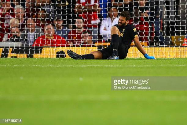 Alisson of Liverpool lies injured during the Premier League match between Liverpool FC and Norwich City at Anfield on August 09 2019 in Liverpool...