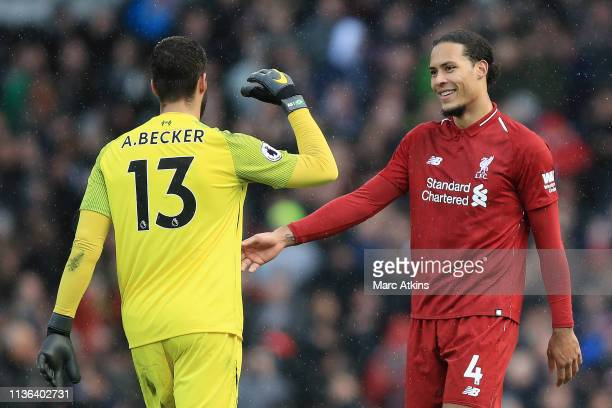 Alisson of Liverpool shakes hands with Virgil van Dijk of Liverpool after the Premier League match between Fulham FC and Liverpool FC at Craven...