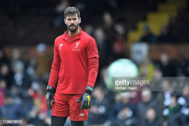 Alisson of Liverpool warms up ahead of the Premier League match between Fulham FC and Liverpool FC at Craven Cottage on March 17 2019 in London...