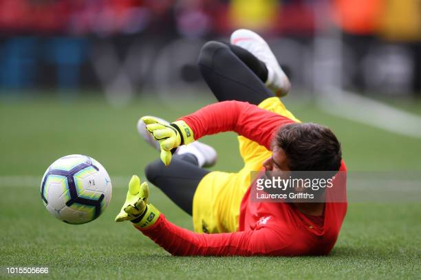 Alisson of Liverpool warms up prior to the Premier League match between Liverpool FC and West Ham United at Anfield on August 12 2018 in Liverpool...