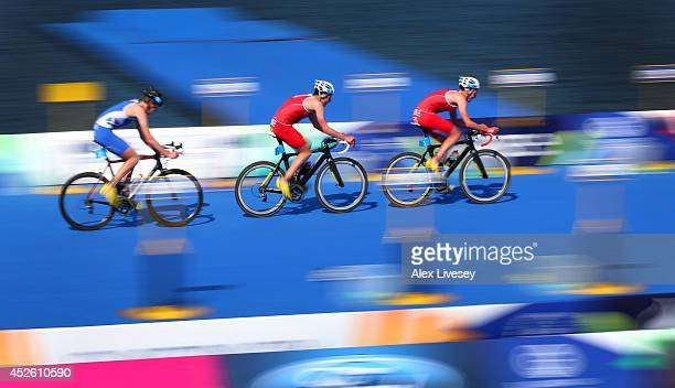 Alistair Brownlee of England leads from Jonathan Brownlee of England and Marc Austin of Scotland during the cycling leg in the Men's Triathlon at...