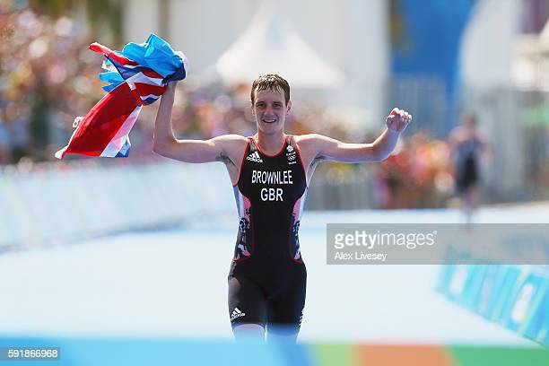 Alistair Brownlee of Great Britain crosses the finish line during the Men's Triathlon at Fort Copacabana on Day 13 of the 2016 Rio Olympic Games on...