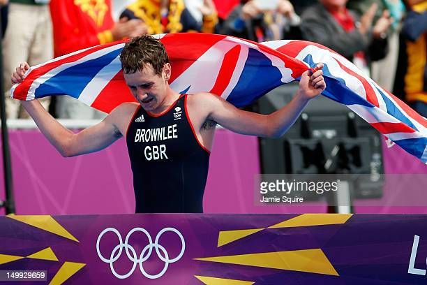 Alistair Brownlee of Great Britain crosses the finish line to win the gold medal in the Men's Triathlon during the Men's Triathlon on Day 11 of the...