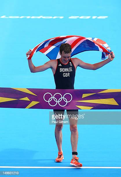 Alistair Brownlee of Great Britain holds a union jack aloft as he celebrates crossing the finish line and winning gold during the Men's Triathlon on...