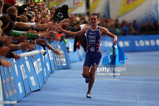Alistair Brownlee of Great Britian celebrates with the crowd as he crosses the line to win the Men's Elite race during day two of the Dextro Energy...