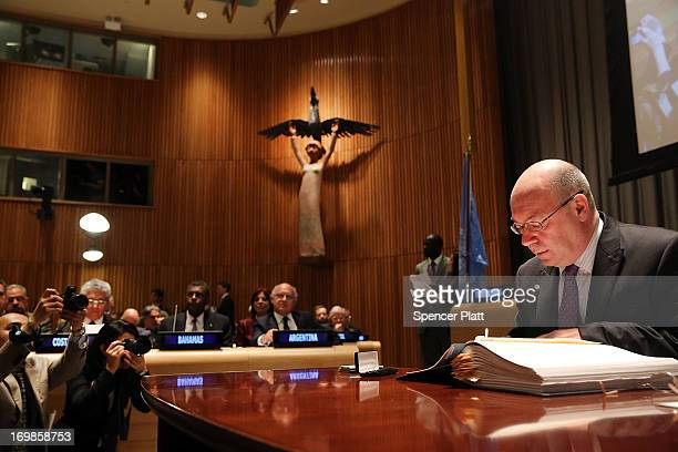 Alistair Burt of the United Kingdom signs the first international treaty regulating global arms trade at the United Nations on June 3 2013 in New...