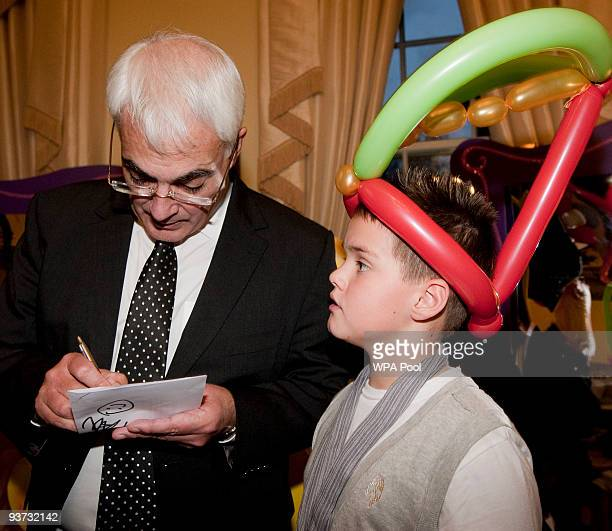 Alistair Darling Chancellor of the Exchequer signs an autograph for a young boy during the Chancellor of the Exchequer's annual children's Christmas...