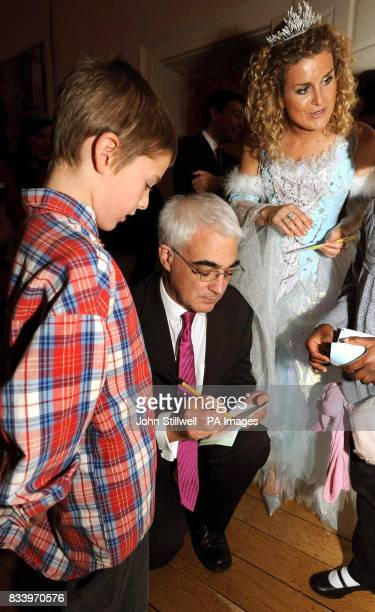 Alistair Darling the Chancellor of the Exchequer kneels down to sign an autograph for a young boy at his annual children's Christmas party at 11...