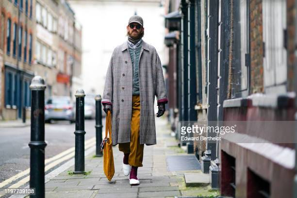 Alistair Guy wears a cap sunglasses a checked long coat brown pants burgundy socks white pointy shoes an orange bag leather gloves a scarf during...