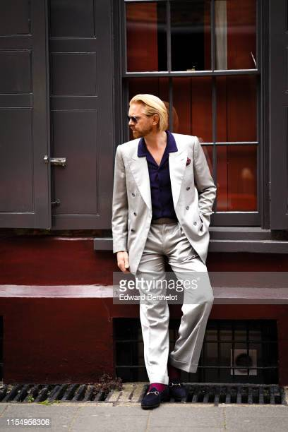 Alistair Guy wears a gray blazer jacket a dark blue shirt flare pants shoes during London Fashion Week Men's June 2019 on June 09 2019 in London...