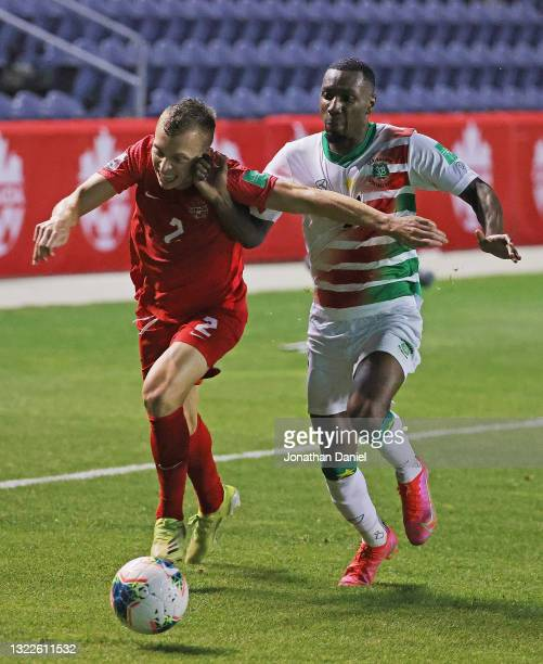 Alistair Johnston of Canada holds off Sheraldo Becker as he advances the ball during a FIFA World Cup Qualifier at SeatGeek Stadium on June 08, 2021...