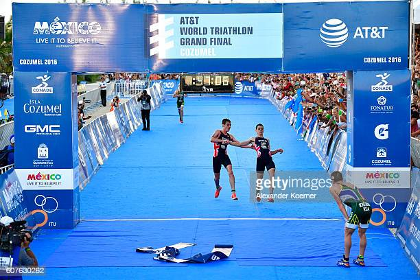 Alistar Brownlee of Great Britain helps his brother Jonathan Brownlee of Great Britain to cross the finished line as Jonathan collapsed of...