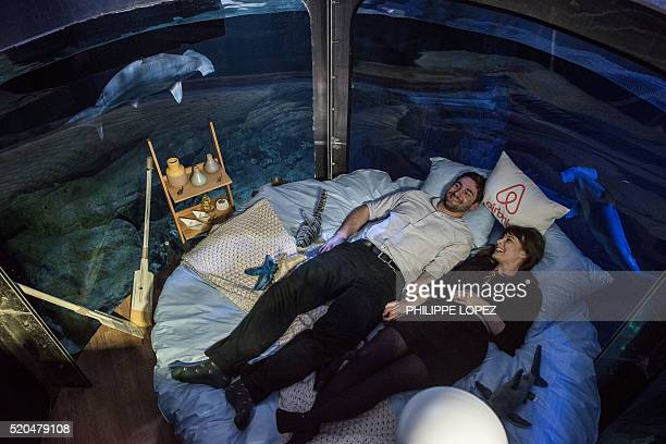 Alister Shipman from Britain and Hannah Simpson from Northern Ireland winners of a competition on the Airbnb accommodation site lie in bed at the...