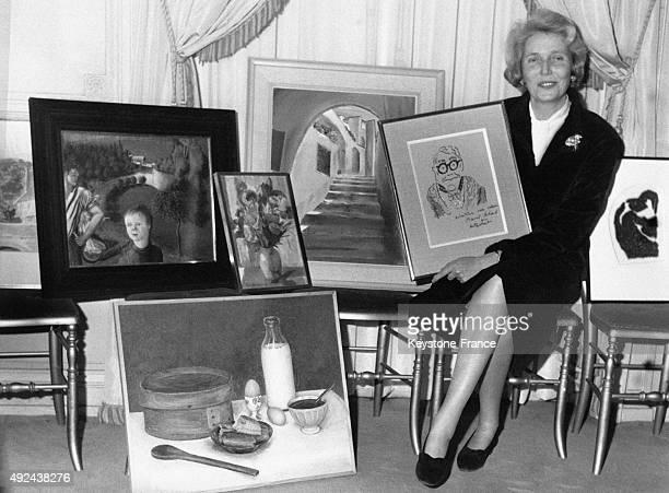 Alix de Rothschild entouree de peintures realisees par des celebrites a l'occasion d'un gala de charite pour l'enfance le 6 janvier 1968